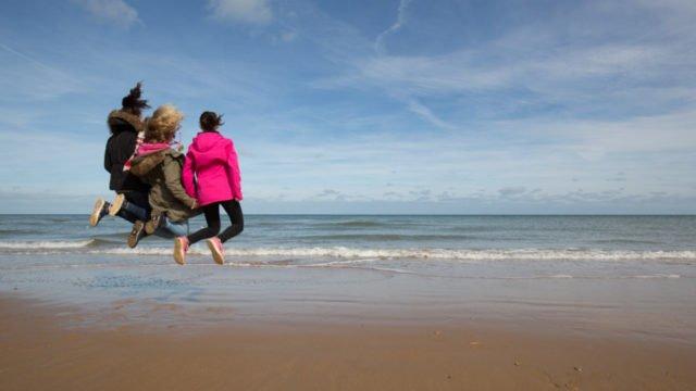 Luftsprünge: An der Küste nutzen die Schüler das gute Wetter und die Bewegungsfreiheit. Foto: SMMP/Beer