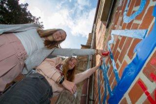"""Die beiden 14-jährigen Engelsburg-Schülerinnen Emma Meyer und Anastasia Lopatta helfen mit, die Außenwand vor der Aula """"demokratisch"""" zu gestalten. Foto: SMMP/Ulrich Bock"""